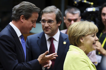 Germany's Chancellor Merkel smiles as Britain's Prime Minister Cameron and Portugal's Prime Minister Passos Coelho talk during the European Union leaders summit in Brussels