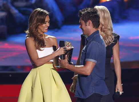 """Zac Efron accepts the award for best shirtless performance for """"That Awkward Moment"""" from presenter Jessica Alba at the 2014 MTV Movie Awards in Los Angeles"""