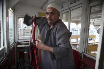A disabled man steers the wheel of a cruise boat on the river Nile in Cairo