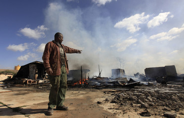 Mabrook al-Hammali points to what used to be his house after a fire went off in a compound for homeless Libyan families in Benghazi