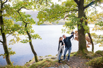Young happy couple stands on the coast of lake and does selfie-photo on the photo camera