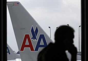A passenger walks by an American Airlines airplane at a gate at the O'Hare Airport in Chicago, Illinois