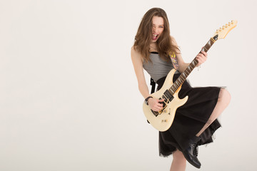 Attractive girl emotionally playing the electric guitar. Beautiful brunette lady playing hard rock music isolated. Musician girl singing with dark lipstick