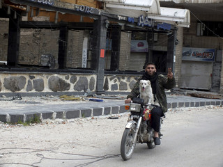 A member of the Free Syrian Army gestures as he rides a motorcycle with a dog in Homs