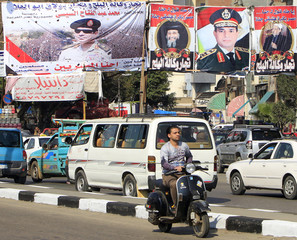 People and their vehicles are caught in a traffic jam in front of banners of Egypt's army chief, Field Marshal Abdel Fattah al-Sisi, with Coptic and Islamic leaders in Cairo