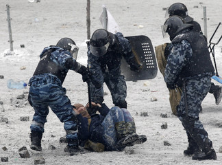 Riot police officers hold a man lying on the ground during clashes between police and pro-European protesters in Kiev
