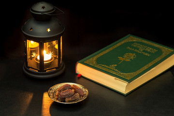 Dates, quran, and lantern at dark