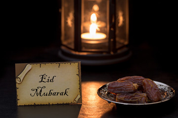 Eid mubarak card with dates and lantern at night