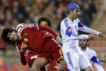 Belgium's Fellaini jumps for the ball with Cyprus' Sielis during their Euro 2016 qualifying match in Brussels