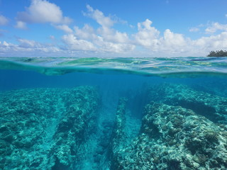 Over under water surface, rocky seabed with coral reef underwater and cloudy blue sky split by waterline, Huahine, Pacific ocean, French Polynesia