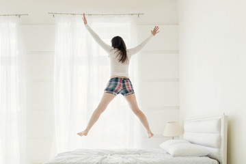 Rear view of young woman jumping up on bed at home