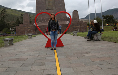 A tourist poses for a picture with a Valentine's Day display at the Middle of the World monument, in Quito, Ecuador