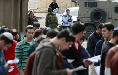 Jewish settlers attend a prayer in Hebron