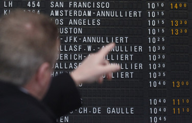 Passenger looks at the flight departure information board at the main terminal of Frankfurt's airport