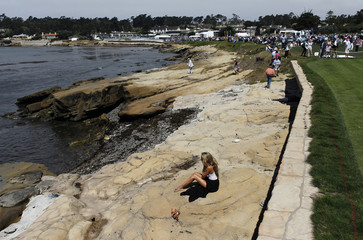 A guest sits on the shore along the 18th fairway during the Concours d'Elegance at the Pebble Beach Golf Links in Pebble Beach