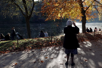 A woman stops to take a picture near an artificial pond and a tree with yellow-colored leaves in the Buttes-Chaumont Park as warm autumn weather continues in Paris