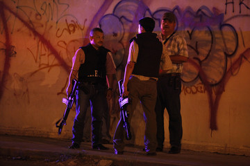 Agents of the investigative police talk outside a bar where two people were gunned down in Monterrey