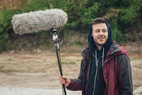 Behind the scene. Sound boom operator hold microphone fisher outdoor