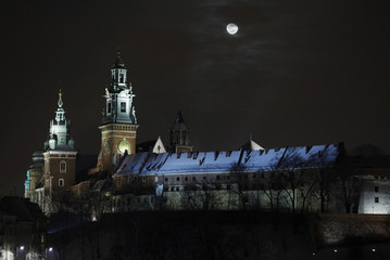 The moon rises over Wawel castle during winter night in Krakow