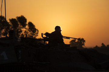 A Israeli soldier sits atop a tank outside the central Gaza Strip