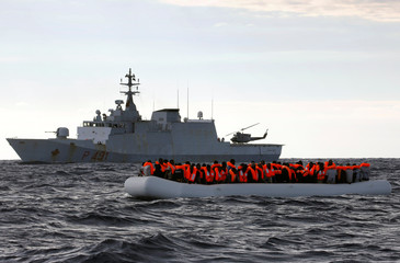 An overcrowded raft carrying African migrants is seen in front of an Italian Navy vessel, as lifeguards from the Spanish NGO Proactiva Open Arms rescue all on aboard, while it drifts out of control in the central Mediterranean Sea