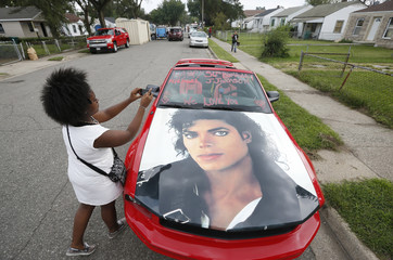A fan of music superstar Michael Jackson takes a picture of a car decorated with a photo of the pop icon outside his childhood home in Gary, Indiana