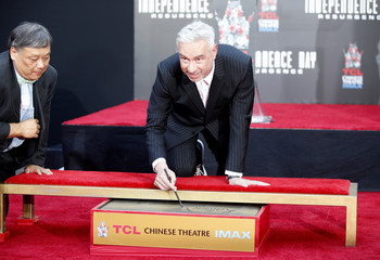 Director Roland Emmerich signs the cement during his Hand and Foot Print Ceremony in Hollywood