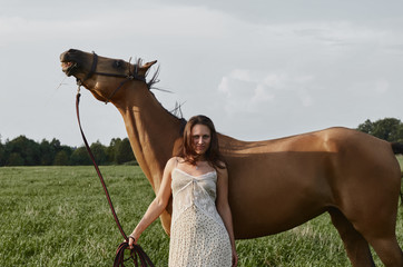 Young seductive attractive Caucasian lady in brown summer dress is posing with beautiful horse in Russian meadow forest background. Cheerful brunette lady is looking at the camera holding the bridle.