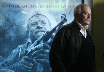 Film director and actor Mikhalkov stands in front of a poster advertising his latest film, Burnt by the Sun II, in Moscow