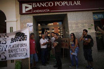 Siles, his brothers, and their father wait to talk to an employee outside a Banco Popular bank branch, to request a meeting to try to stop their evictions and get a pardon for their mortgages, in Sabinillas