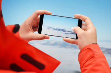 Man taking photo on top of mountain with smartphone