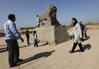Residents visit a statue of the Lion of Babylon near Hilla