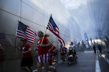 Members of the Red White and Blue team run through the 9/11 Empty Sky memorial at sunrise across from New York's Lower Manhattan and One World Trade Center, in Liberty State Park in Jersey City, New Jersey