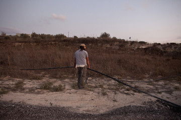 A Jewish settler tries to fix a water pipe to get water to his home at the unauthorized outpost of Havat Gilad, south of Nablus