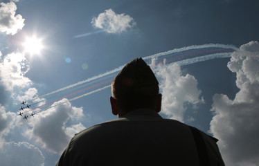 A serviceman watches as the Royal Air Force aerobatic team perform during an air show at Zhukovsky