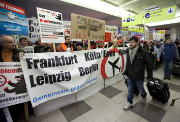 Arriving travellers walk past demonstrators who rally against aircraft noise and night-flights in a terminal of Schoenefeld airport ouside of Berlin