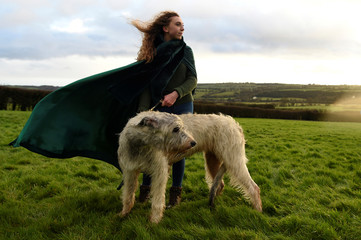 Rebecca Smith poses for a photograph during winter solstice with her Irish Wolfhound dog called Amazing Grace at the 5000 year old stone age tomb of Newgrange (not in view) in the Boyne Valley at sunrise in Newgrange