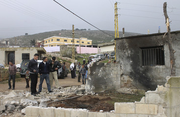 Residents inspect a damaged house in Wadi Khaled town after shelling by Syrian forces towards villagers' houses, in north Lebanon