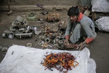 A scrap worker breaks a electric motors apart in order to retrieve metal wires for sale at a roadside stall in Faisalabad