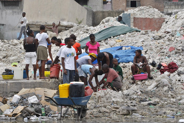 Haitians collect water from a public source after four days of protest in Port-au-Prince