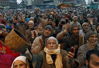 Kashmiri Muslims raise their arms in prayers upon seeing a relic of Sheikh Abdul Qadir Jeelani, a Sufi saint, on his death anniversary outside his shrine in Srinagar