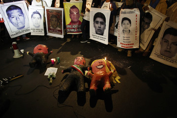 "'Pinatas"" depicting Mexico's President Pena Nieto, his wife Rivera and Attorney General Murillo Karam, are seen on the floor next to pictures of the 43 missing students of the Ayotzinapa Teacher Training College during a protest in Mexico City"