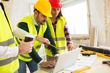 Architects using laptop at construction site