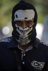 Member of the community police poses for a picture after breaking into the village of Paracuaro, and taking over control, in Michoacan state
