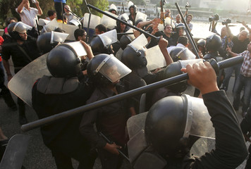 Riot police attempt to separate anti-Mursi protesters and supporters of Egyptian President Mohamed Mursi in front of the Ministry of Culture during a demonstration in Cairo