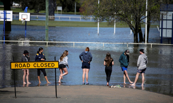 Local children wade in the overflowing Lachlan River after heavy rain burst its banks with a natural disaster zone declared in the midwestern New South Wales town of Forbes