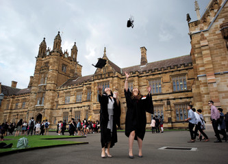School of Business graduates toss their hats into the air for family members to take pictures outside the main building at the University of Sydney in Australia