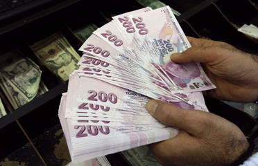 A money changer counts Turkish lira bills at an currency exchange office in Istanbul