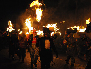 Participants carrying burning barrels of tar on their heads parade through Allendale