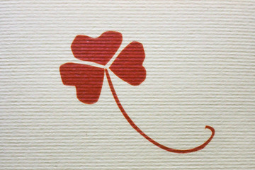 Three petals of clovers, a graceful plant with a long curved arch, a painted image of a red color, on rough paper with striped relief design texture.